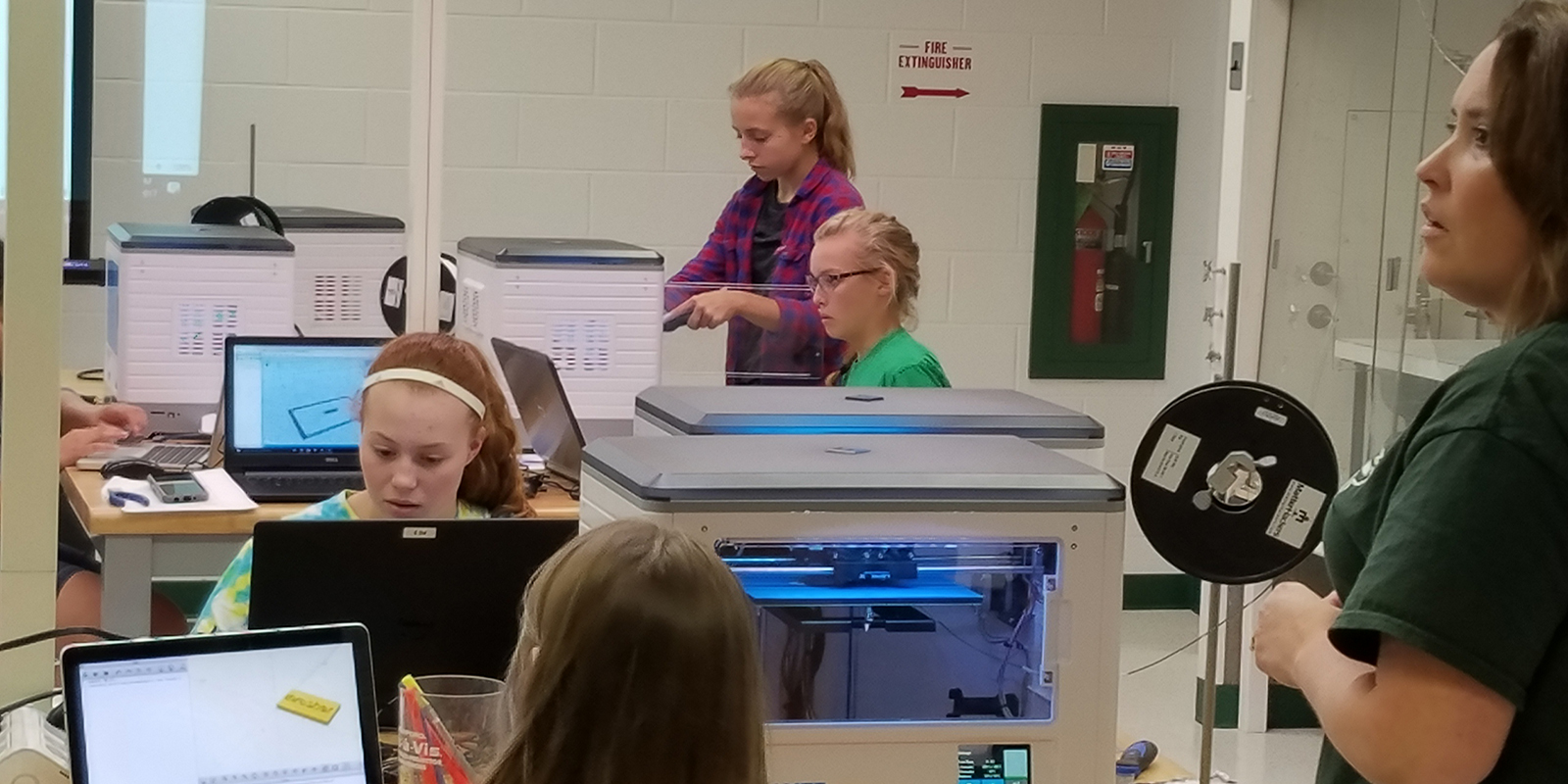 Middle school girls and their teacher in a computer lab using 3D printers