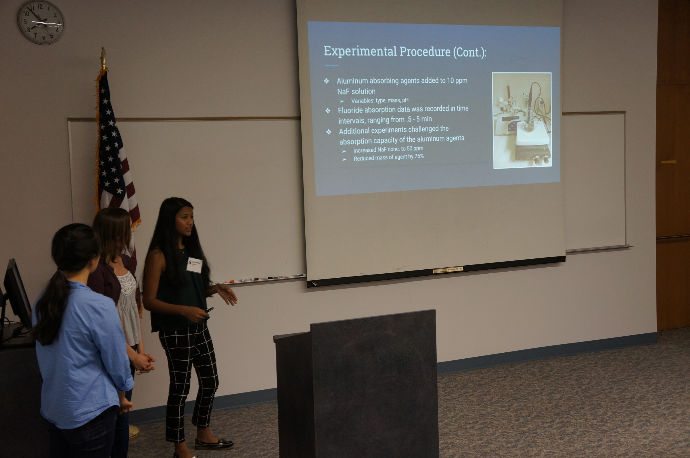 Three students presenting in front of a group