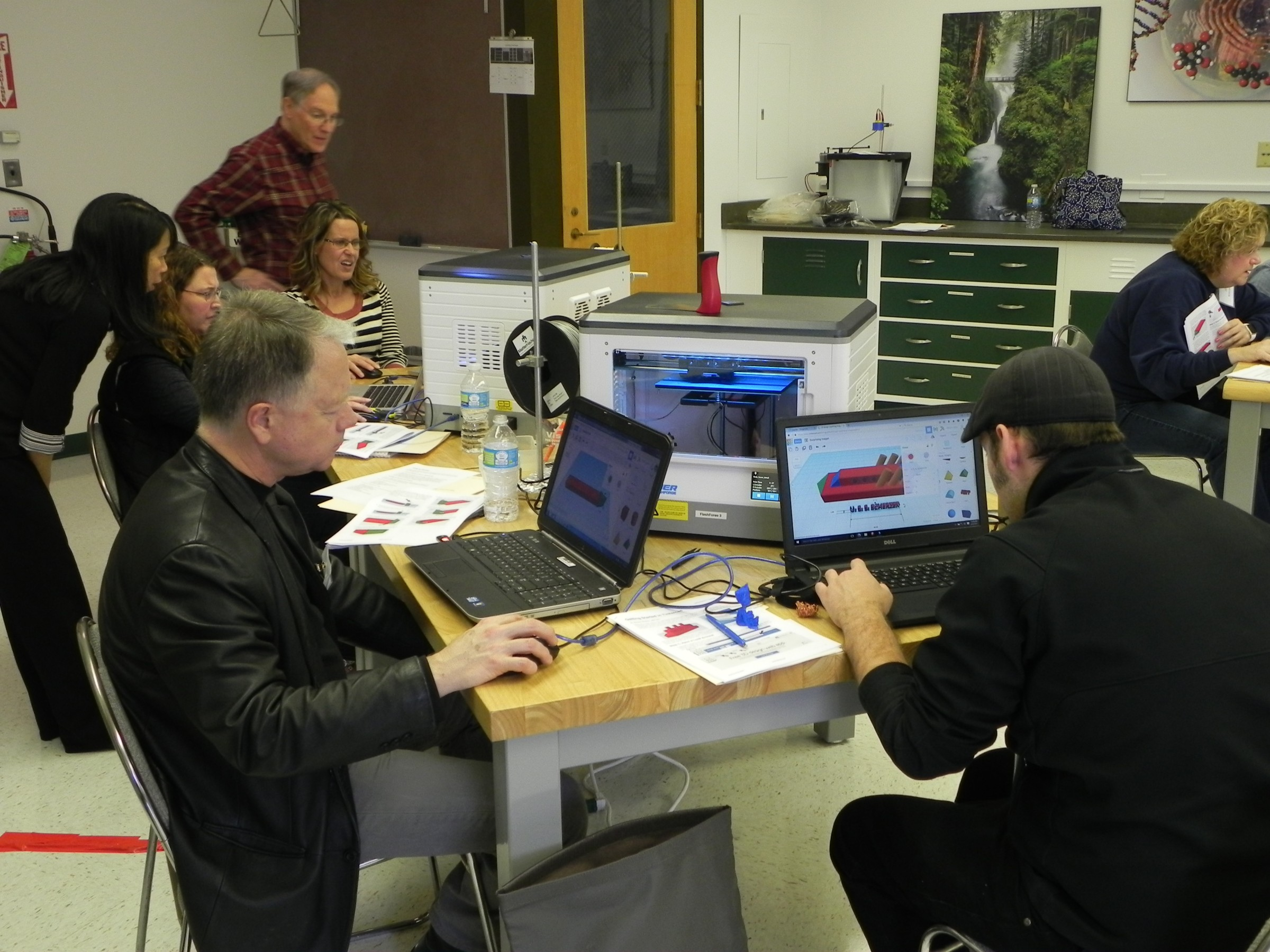 Teachers using 3D printers in a workshop setting