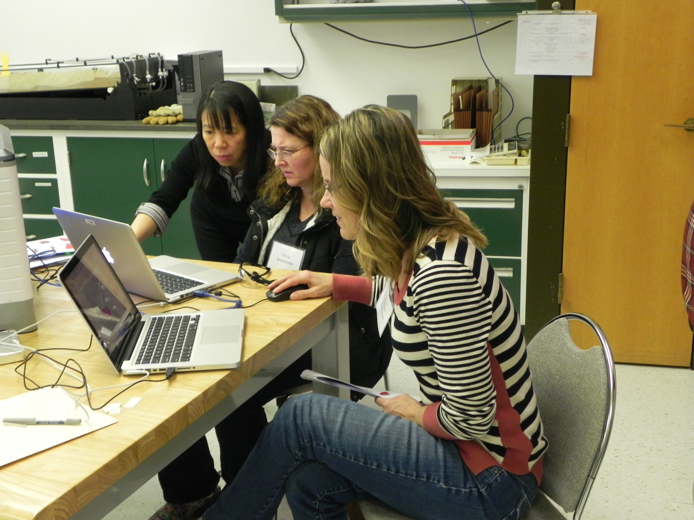 Three women working on project on laptop
