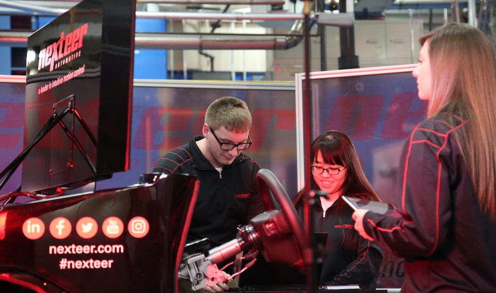 Nexteer employees working on simulator in plant