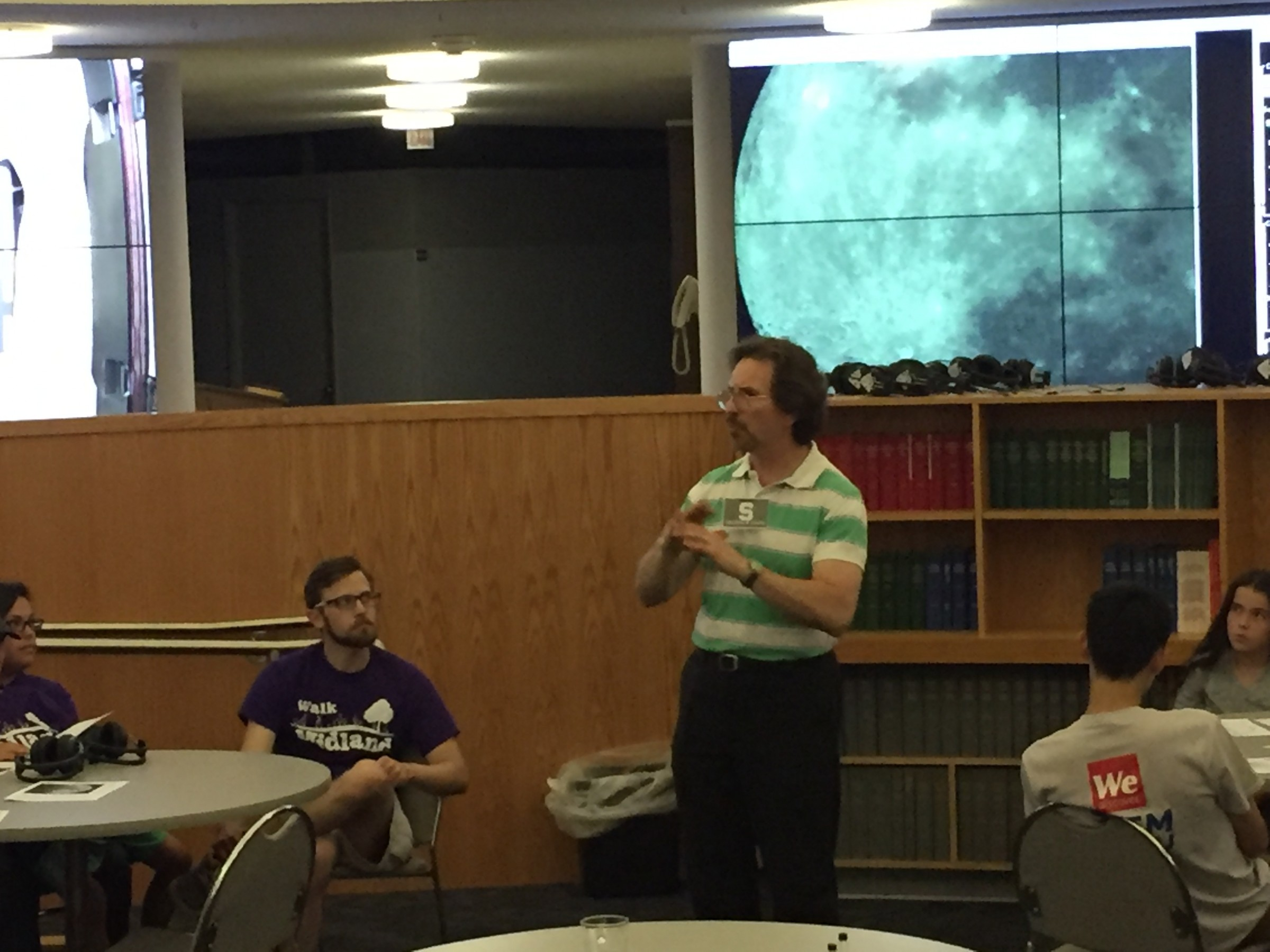 Researcher explains astronomy lesson with moon photo in background