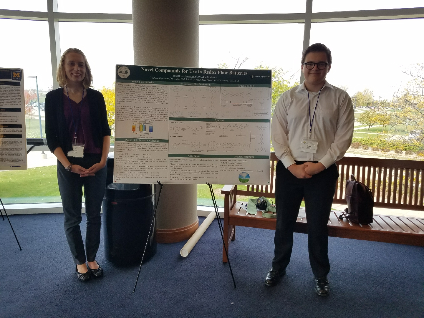 Two students present poster at a conference