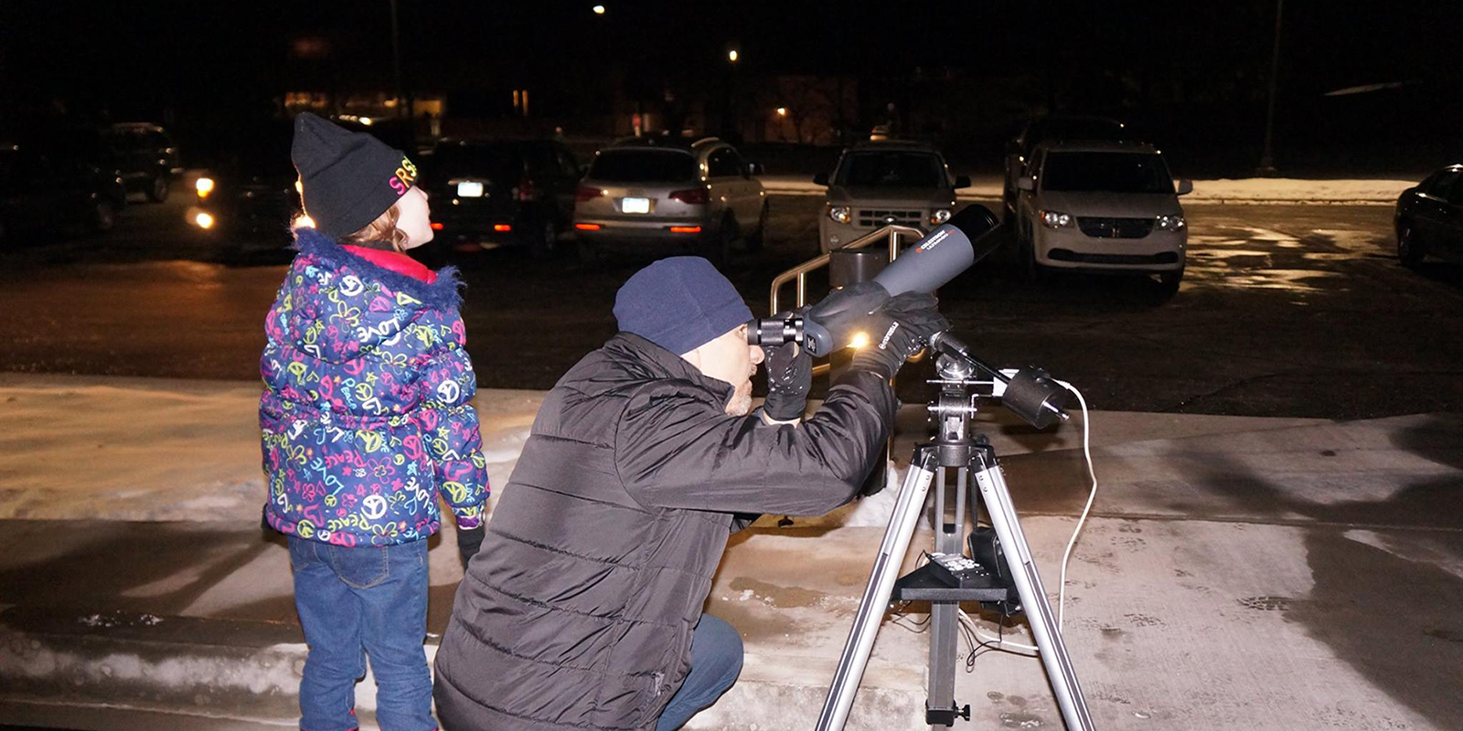 Instructor showing child how to use telescope during evening educational event