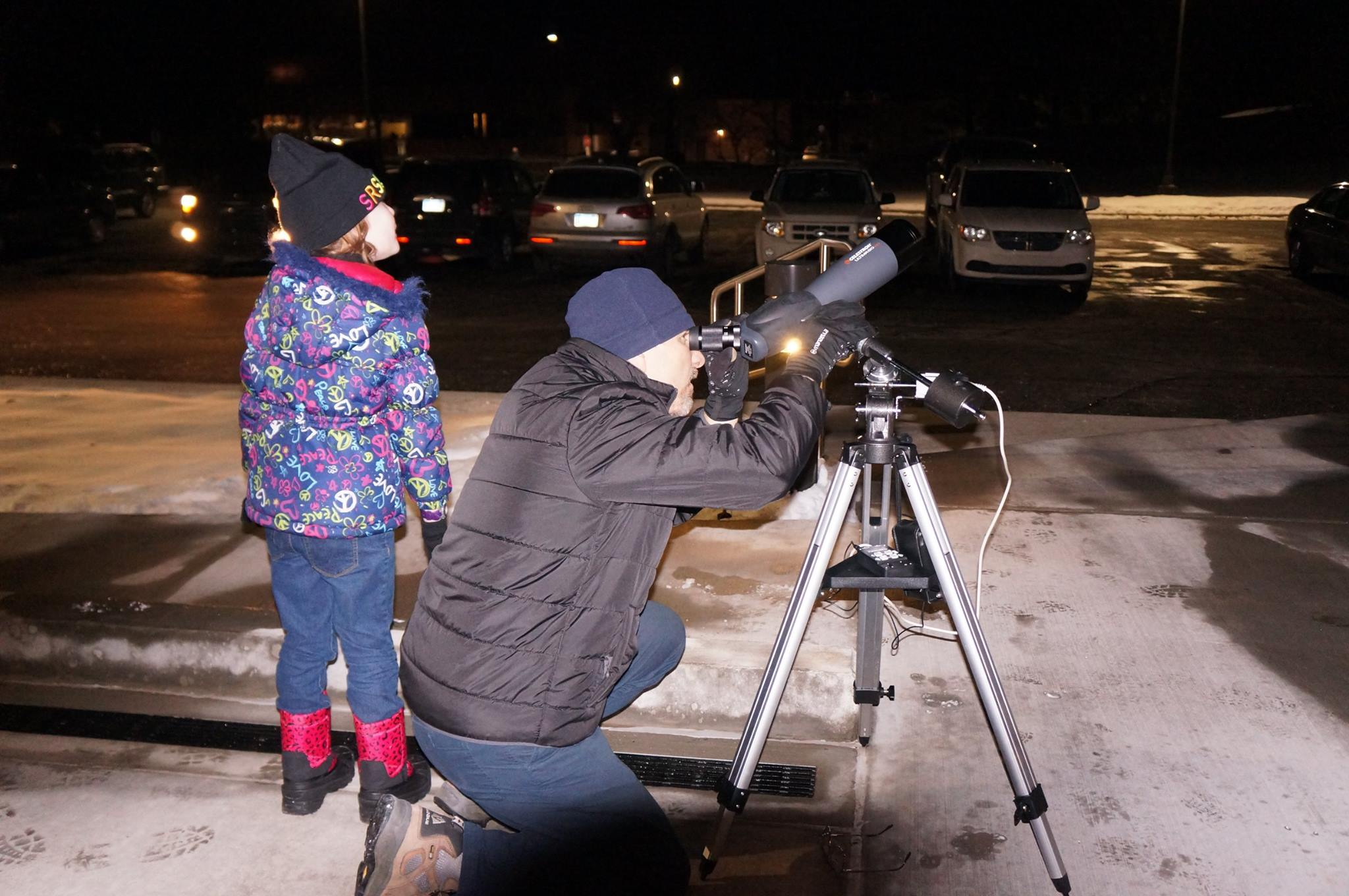Astronomer and child using a telescope