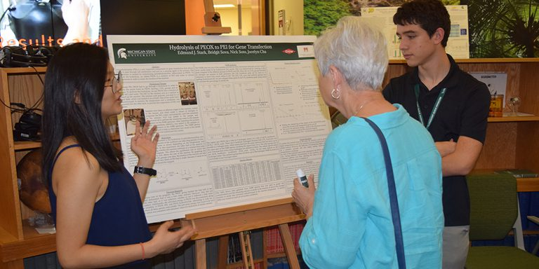 Students present research poster to guest during reception